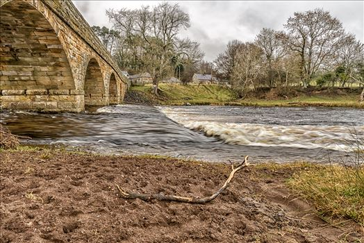This is an old bridge built by the Duke of Northumberland and then adopted by the County in 1888. It spans the River Coquet at Paperhaugh, nr Rothbury, Northumberland.